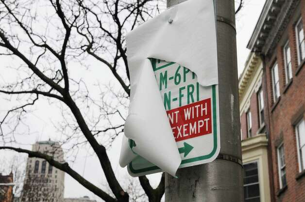 A partially covered permit parking sign is seen on State Street, Monday Dec. 10, 2012, in Albany, N.Y. The new tentative date for the start of Albany?s downtown parking permit system is Jan. 15. (Will Waldron / Times Union) Photo: Will Waldron