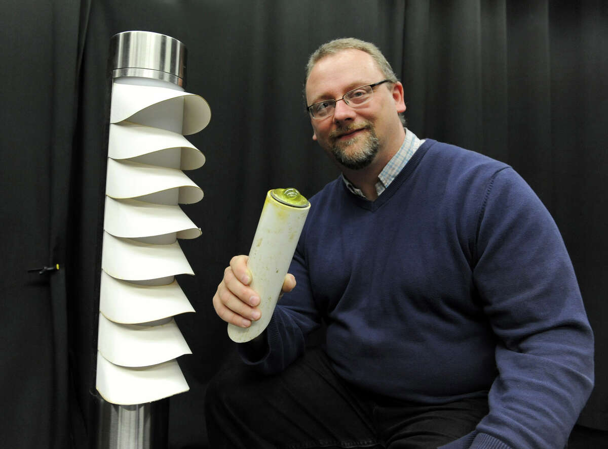 John Bullough, senior research scientist, sits next to a pedestrian bollard fixture which is new lighting for use at roundabouts which was developed by the Lighting Research Center on Friday Nov. 30, 2012 in Troy, N.Y. In his hand is a retro reflective curve marker which is activated by light going in one direction and coming out the same direction. This is placed in the inside grassy area of a roundabout. (Lori Van Buren / Times Union)