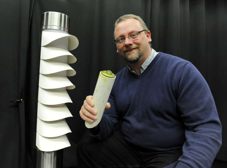 John Bullough, senior research scientist, sits next to a pedestrian bollard fixture which is new lighting for use at roundabouts which was developed by the Lighting Research Center on Friday Nov. 30, 2012 in Troy, N.Y. In his hand is   a retro reflective curve marker which is activated by light going in one direction and coming out the same direction. This is placed in the inside grassy area of a roundabout. (Lori Van Buren / Times Union) Photo: Lori Van Buren