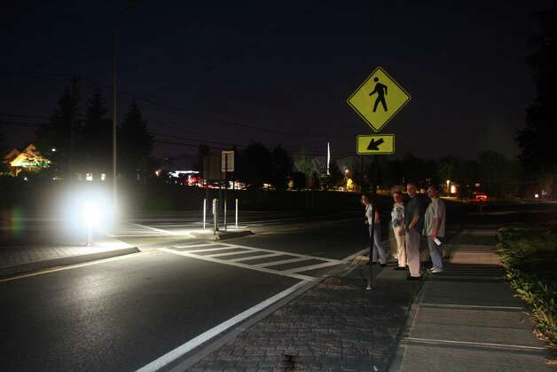 Pedestrians stand by a Bethlehem crosswalk illuminated with experimental lighting this summer. (Lighting Research Insitute photo.)