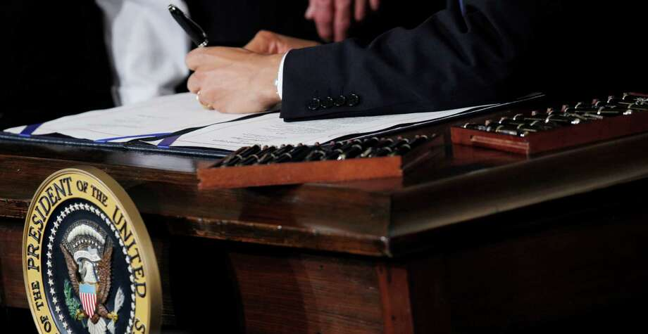 FILE - This March 23, 2010 file photo shows Ttwenty two pens next to President Barack Obama as he signs the health care reform bill in the East Room of the White House in Washington. Your medical plan is  facing an unexpected expense, so you probably are, too. It's a new, $63-per-head fee to cushion the cost of covering people with pre-existing conditions under President Barack Obama's health overhaul. The charge, buried in a recent regulation, works out to tens of millions of dollars for the largest company health plans, and much of that is likely to be passed on to employees. Multiple pens are used to sign legislation, and then distributed to supporters of the legislation. (AP Photo/Charles Dharapak, File) Photo: Charles Dharapak