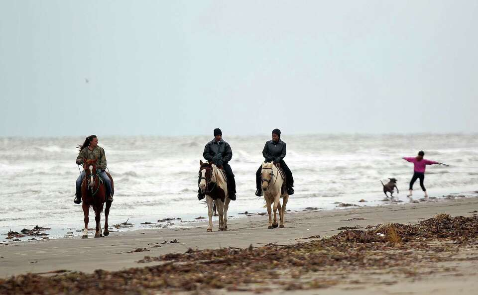 Nicole Glenn with S-n-G Horseback Riding leads Angela Smith and Gerard Daniels of Houston on a beach