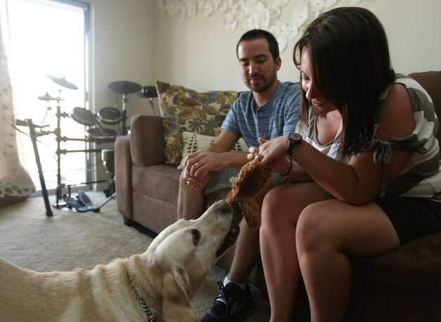 Natalie Garza plays with her husband Darrell's guide dog Monday August 13, 2012 in their home. Natalie is an apprentice guide dog mobility instructor with the Guide Dogs of Texas, and was inspired become an instructor after finding Egypt three years ago. Photo: Julysa Sosa, San Antonio Express-News / © 2012 San Antonio Express-News
