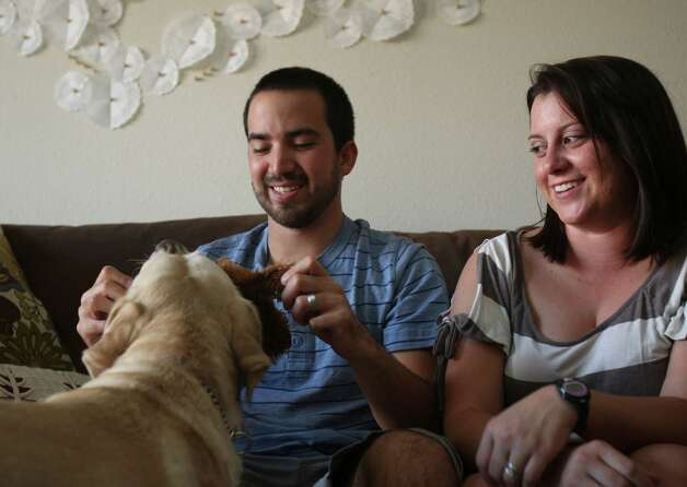 Darrell Garza plays with his guide dog Egypt, Monday August 13, 2012 with his wife Natalie Garza who is an apprentice guide dog mobility instructor with the Guide Dogs of Texas in their home. Photo: Julysa Sosa, San Antonio Express-News / © 2012 San Antonio Express-News