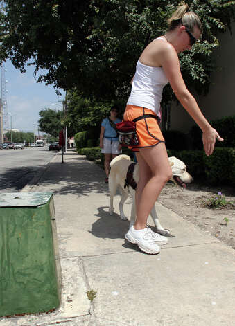 "Jamie Landy, an instructor with Guide Dogs of Texas, motions to ""Seymour"", a guide dog in training, to avoid an obstacle on the sidewalk during a training session in the downtown area of San Antonio, Wednesday, Aug. 8, 2007. Photo: Bob Owen, San Antonio Express-News / SAN ANTONIO EXPRESS-NEWS"
