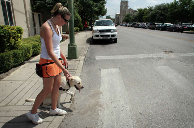 "Jamie Landy, an instructor with Guide Dogs of Texas, motions forward to guide dog ""Seymour"" during a walking training session in the downtown area of San Antonio, Wednesday, Aug. 8, 2007. Photo: Bob Owen, San Antonio Express-News / SAN ANTONIO EXPRESS-NEWS"