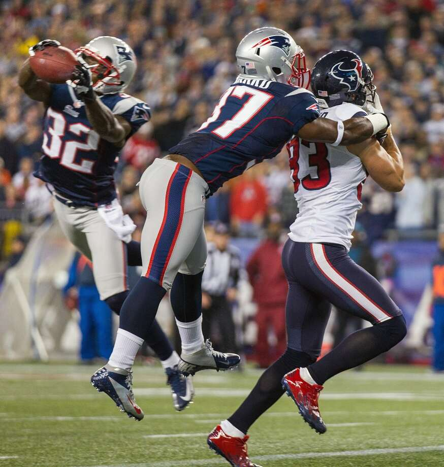 Patriots free safety Devin McCourty (32) intercepts a pass intended for Texans wide receiver Kevin Walter (83) in the end zone as Patriots cornerback Alfonzo Dennard (37) defends during the first quarter. (Brett Coomer / Houston Chronicle)