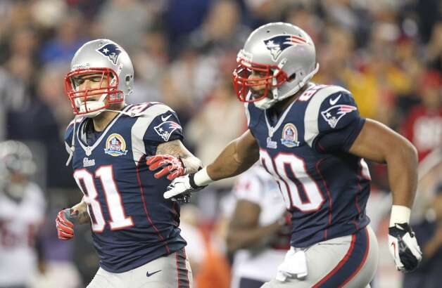 Patriots tight end Aaron Hernandez (81) celebrates with tight end Visanthe Shiancoe (80) after catching a 7-yard touchdown pass. (Nick de la Torre / Houston Chronicle)