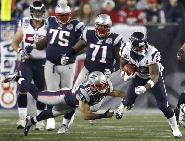Texans running back Arian Foster (23) tries to slip past Patriots strong safety Steve Gregory (28). (Brett Coomer / Houston Chronicle)