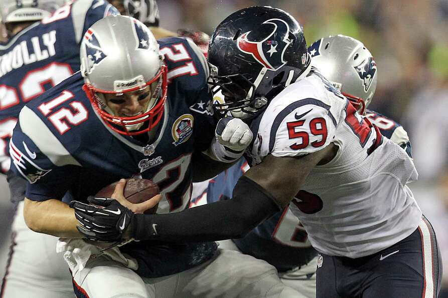 Patriots quarterback Tom Brady (12) is sacked by Texans linebacker Whitney Mercilus (59) during the