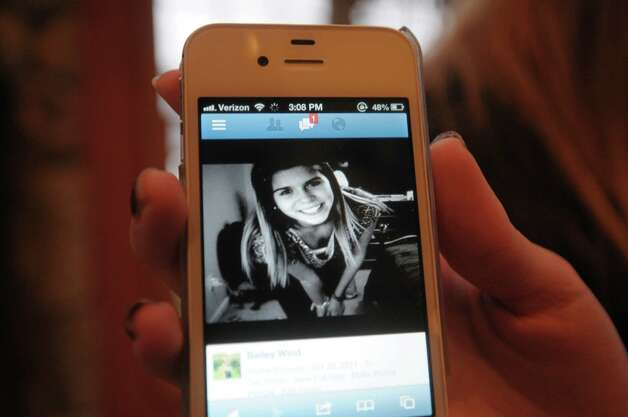 Nikki Wind shows a photograph of her sister, Bailey, on her phone at their home on Monday, Dec. 10, 2012 in Latham, NY.  This was the photograph that Chris Stewart first saw of Bailey when he became interested in getting to know her.  Chris connected with her on Facebook and they started texting every day before going out on a date.    Bailey was in the traffic accident which took the lives of her boyfriend, Chris Stewart, and their friend Deanna Rivers.  (Paul Buckowski / Times Union) Photo: Paul Buckowski