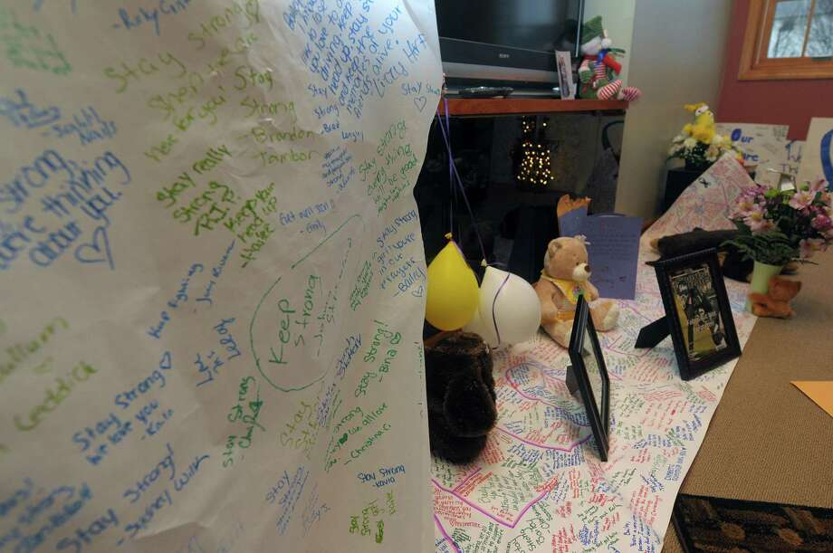 Messages written on large sheets of paper and photographs and gifts line the floor at the home of Bailey Wind seen here on Monday, Dec. 10, 2012 in Latham, NY.   Bailey was in the traffic accident which took the lives of her boyfriend, Chris Stewart, and their friend Deanna Rivers.  (Paul Buckowski / Times Union) Photo: Paul Buckowski