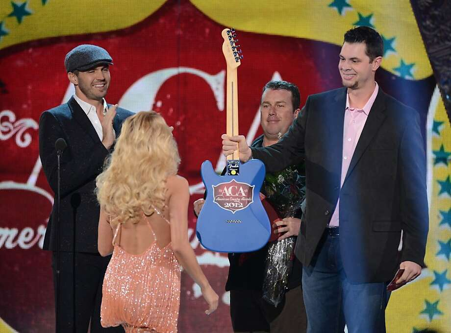 LAS VEGAS, NV - DECEMBER 10: Singer Carrie Underwood (C) accepts the award for Artist of the Year from presenters Barry Zito (L), Rodney Carrington and Brandon Belt (R) onstage during the 2012 American Country Awards at the Mandalay Bay Events Center on December 10, 2012 in Las Vegas, Nevada.  (Photo by Mark Davis/Getty Images) Photo: Mark Davis, Getty Images