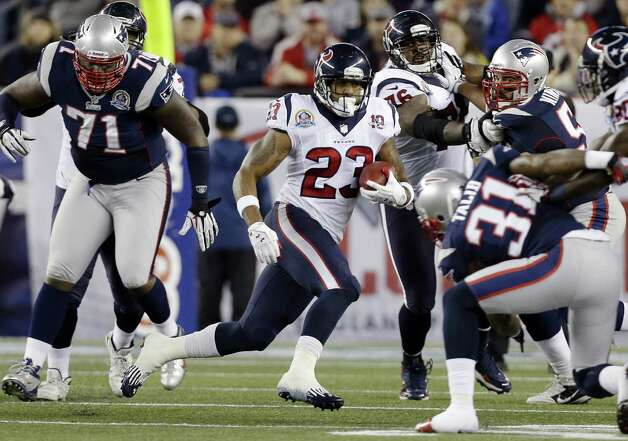 Houston Texans running back Arian Foster (23) rushes between New England Patriots defensive tackle Brandon Deaderick (71) and cornerback Aqib Talib (31) during the first quarter of an NFL football game in Foxborough, Mass., Monday, Dec. 10, 2012. (AP Photo/Elise Amendola) Photo: Elise Amendola, Associated Press / AP