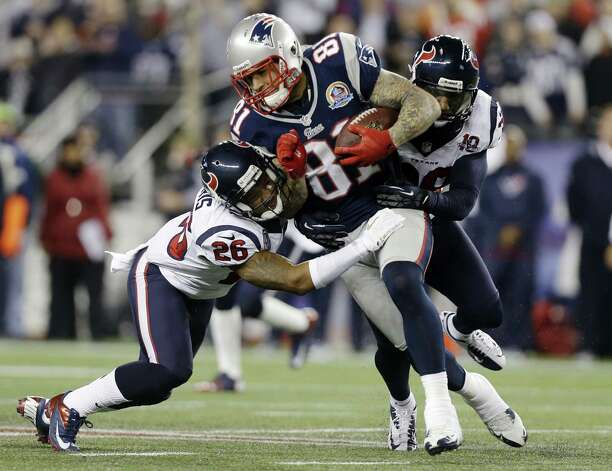 New England Patriots tight end Aaron Hernandez (81) gains yards after a catch against Houston Texans defensive back Brandon Harris (26) and free safety Danieal Manning (38) during the second quarter of an NFL football game in Foxborough, Mass., Monday, Dec. 10, 2012. (AP Photo/Elise Amendola) Photo: Elise Amendola, Associated Press / AP