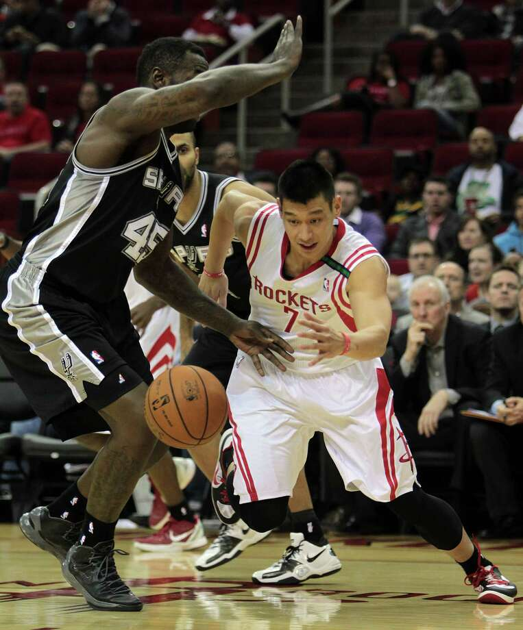 The Rockets' Jeremy Lin (7) drives past the Spurs' DeJuan Blair in the first half of Monday's game at Toyota Center. Lin scored 38 points to match a career high. Photo: James Nielsen, Staff / © Houston Chronicle 2012