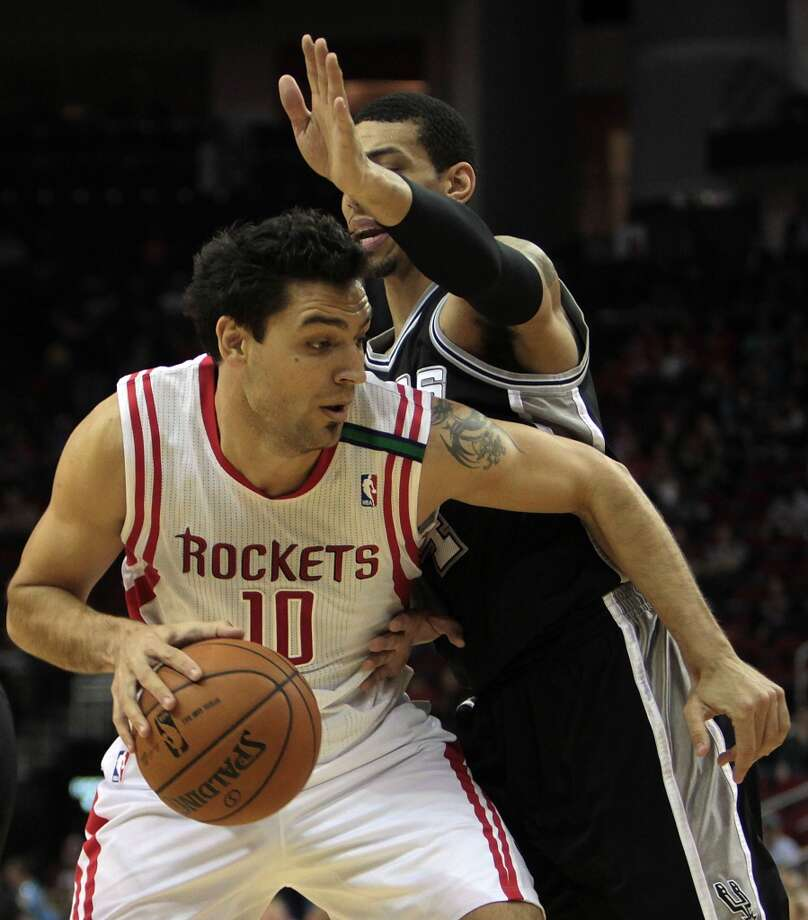 Rockets forward Carlos Delfino is defended by Danny Green of the Spurs. (James Nielsen / Houston Chronicle)