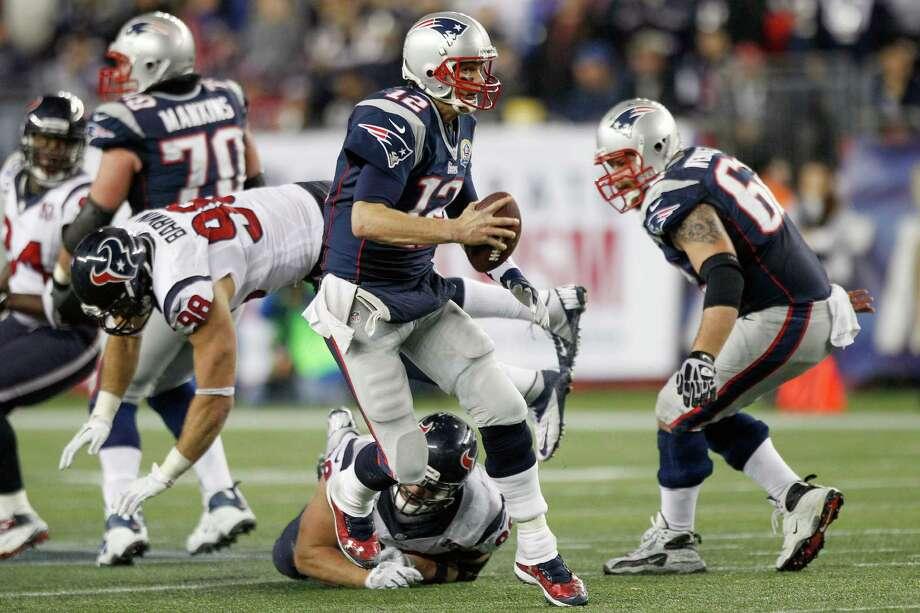 Patriots quarterback Tom Brady (12) scrambles away from Houston Texans defensive end J.J. Watt (99) and outside linebacker Connor Barwin (98). Photo: Brett Coomer, Houston Chronicle / © 2012  Houston Chronicle