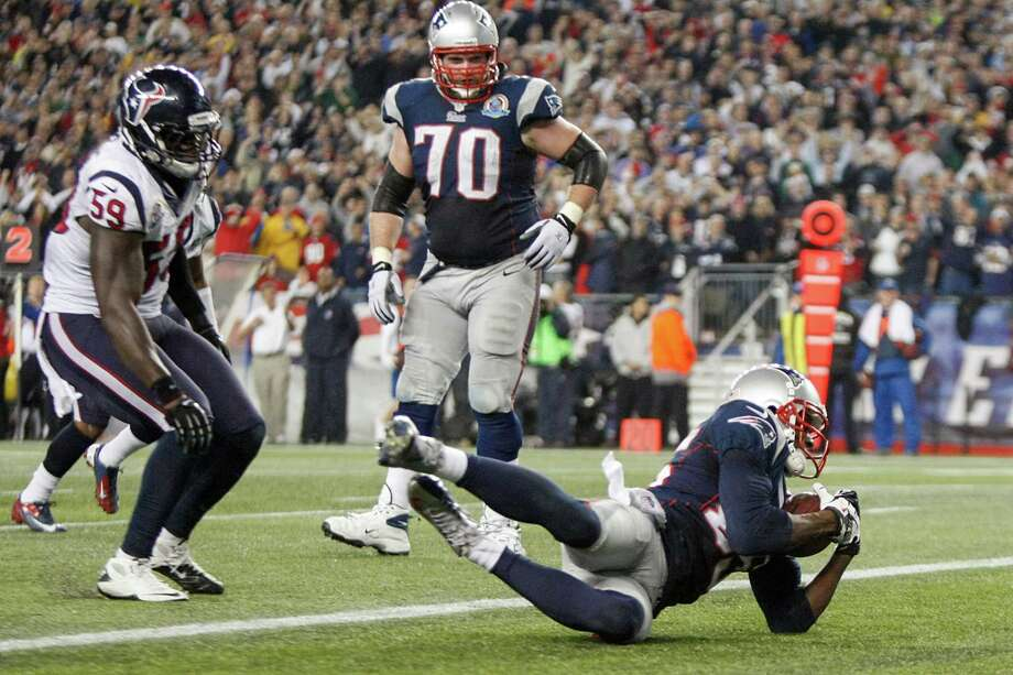 Patriots wide receiver Brandon Lloyd (85) recovers a fumble by running back Danny Woodhead in the end zone for a touchdown as Texans outside linebacker Whitney Mercilus (59) looks on during the fourth quarter. Photo: Nick De La Torre, Houston Chronicle / © 2012  Houston Chronicle