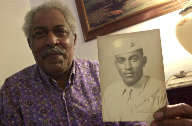 Calvin T. Curtis holds a photo of himself taken wile he was a Marine on May 17, 2000. Photo: Express-News File Photo / EN