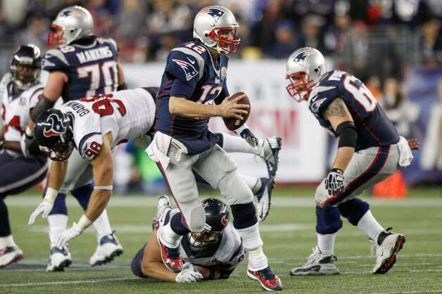 Patriots quarterback Tom Brady (12) scrambles away from Houston Texans defensive end J.J. Watt (99) and outside linebacker Connor Barwin (98). (Brett Coomer / Houston Chronicle)