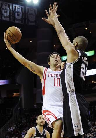 Houston Rockets' Carlos Delfino (10) tries to shoot over San Antonio Spurs' Tim Duncan (21) in the first half of an NBA basketball game, Monday, Dec. 10, 2012, in Houston. (AP Photo/Pat Sullivan) (Associated Press)