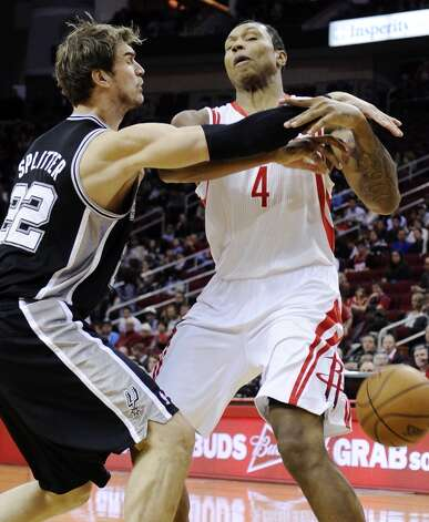 San Antonio Spurs' Tiago Splitter (22) knocks the ball away from Houston Rockets' Greg Smith (4) in the first half of an NBA basketball game, Monday, Dec. 10, 2012, in Houston. (AP Photo/Pat Sullivan) (Associated Press)