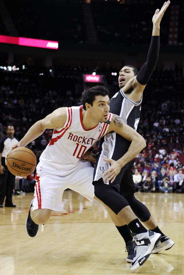 Houston Rockets' Carlos Delfino (10) makes his way around San Antonio Spurs' Danny Green, right, in the first half of an NBA basketball game, Monday, Dec. 10, 2012, in Houston. (AP Photo/Pat Sullivan) (Associated Press)