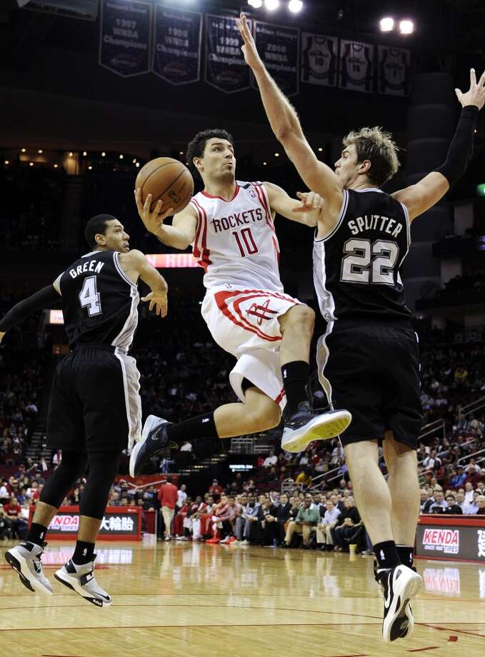 Houston Rockets' Carlos Delfino (10) goes to the basket between San Antonio Spurs' Danny Green (4) and Tiago Splitter (22) in the first half of an NBA basketball game, Monday, Dec. 10, 2012, in Houston. (AP Photo/Pat Sullivan) (Associated Press)