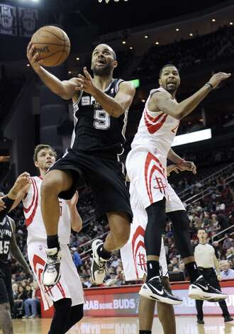 San Antonio Spurs' Tony Parker (9) goes to the basket between Houston Rockets' Chandler Parsons, left, and Marcus Morris (2) in the second half of an NBA basketball game, Monday, Dec. 10, 2012, in Houston. The Spurs won in overtime 134-126. (AP Photo/Pat Sullivan) (Associated Press)