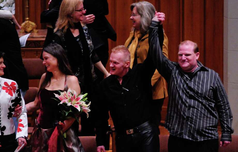 A couple raises their arms together in celebration after getting married during a Service of Marriage at the First Baptist Church on Capitol Hill in Seattle on Sunday, December 9, 2012. 25 same-sex couples were wed in a historic celebration on the first day they were legally allowed to marry. Photo: LINDSEY WASSON / SEATTLEPI.COM