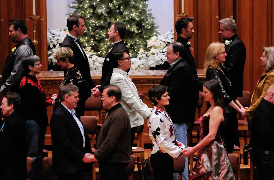 Couples exchange vows during a Service of Marriage at the First Baptist Church on Capitol Hill in Seattle. 25 same-sex couples were wed in a historic celebration on the first day they were legally allowed to marry. Photo: LINDSEY WASSON / SEATTLEPI.COM