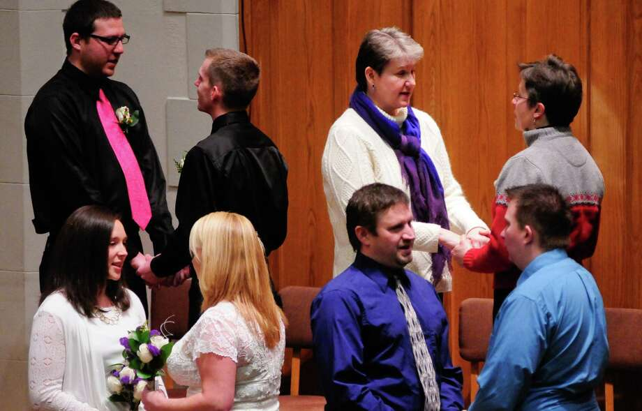 Couples hold hands as they prepare to exchange vows at the First Baptist Church. Photo: LINDSEY WASSON / SEATTLEPI.COM