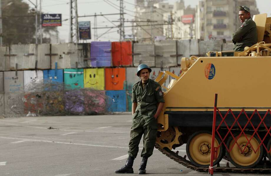 Soldiers stand guard by an armored vehicle in front of the Presidential Palace in Cairo, Egypt, Monday, Dec. 10, 2012. The Egyptian military on Monday assumed joint responsibility with the police for security and protecting state institutions until the results of a Dec. 15 constitutional referendum are announced. (AP Photo/Petr David Josek) Photo: Petr David Josek