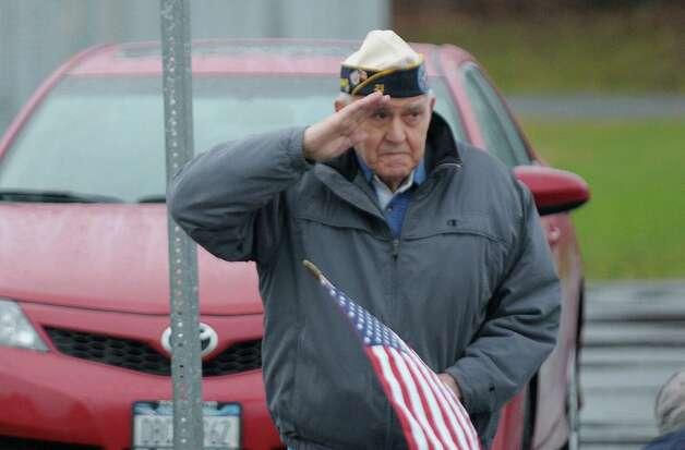 Navy veteran Chris Sgambati, who served in World War II, salutes as the motorcade with the hearse carrying the body of Marine Corps Lance Cpl. Anthony Denier passes by on  Monday, Dec. 10, 2012 in Mechanicville, NY.  Lance Cpl. Denier was killed by enemy fire while on patrol Dec. 2. in Marjah, Afghanistan.   (Paul Buckowski / Times Union) Photo: Paul Buckowski  / 00020401A