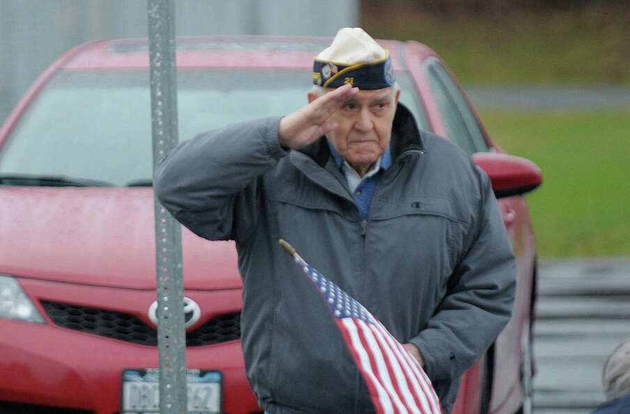 Navy veteran Chris Sgambati, who served in World War II, salutes as the motorcade with the hearse ca