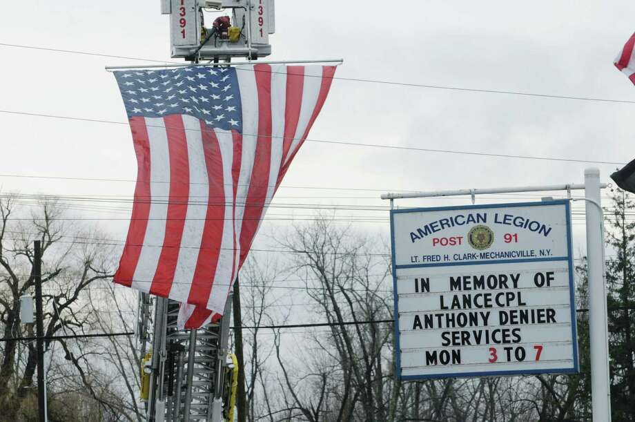 A large flag hangs from the ladder of a fire truck outside of the  American Legion Lt. Fred Clark Post 91 on Monday, Dec. 10, 2012 in Mechanicville, NY.  The service for Marine Corps Lance Cpl. Anthony Denier will be held at the Legion Post on Tuesday.   Lance Cpl. Denier was killed by enemy fire while on patrol Dec. 2. in Marjah, Afghanistan.   (Paul Buckowski / Times Union) Photo: Paul Buckowski  / 00020401A