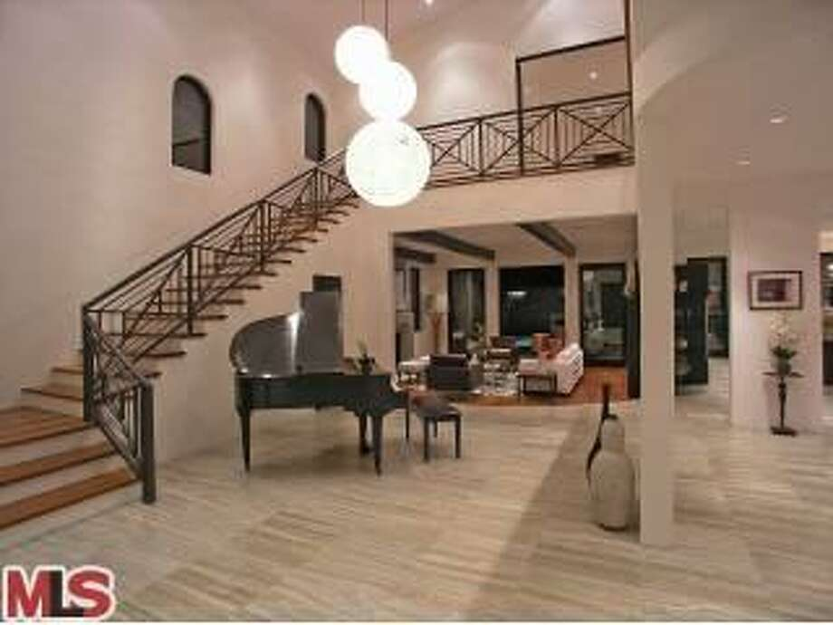 This stately foyer looks a lot different now that the Pacquiao family lives there and large photos are hung below the landing and on nearly every other vertical surface. (Redfin)