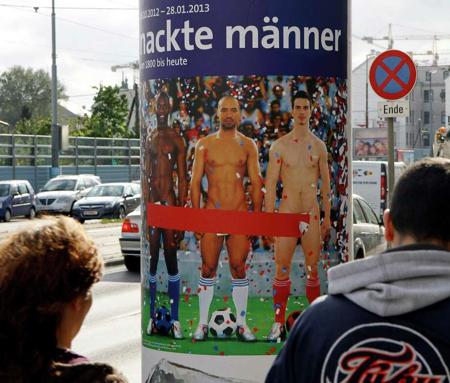 "FILE - In this Oct. 18, 2012 file photo two people walk past a poster showing three naked men which has had red tape added to cover the sensitive parts of the three men, in Vienna, Austria. Poster reads: ""Naked Men"". A prestigious Vienna museum, The Leopold Museum, says a man took the concept of life imitating art to an extreme recently when he suddenly stripped at an exhibition of pictures and sculptures portraying nude men through the ages. A museum spokesman said Tuesday Dec. 11, 2012 that after taking his clothes off, the man calmly sauntered through the exhibition, dressing again only after a security guard asked him to do so. (AP Photo/Ronald Zak, File) Photo: Ronald Zak"