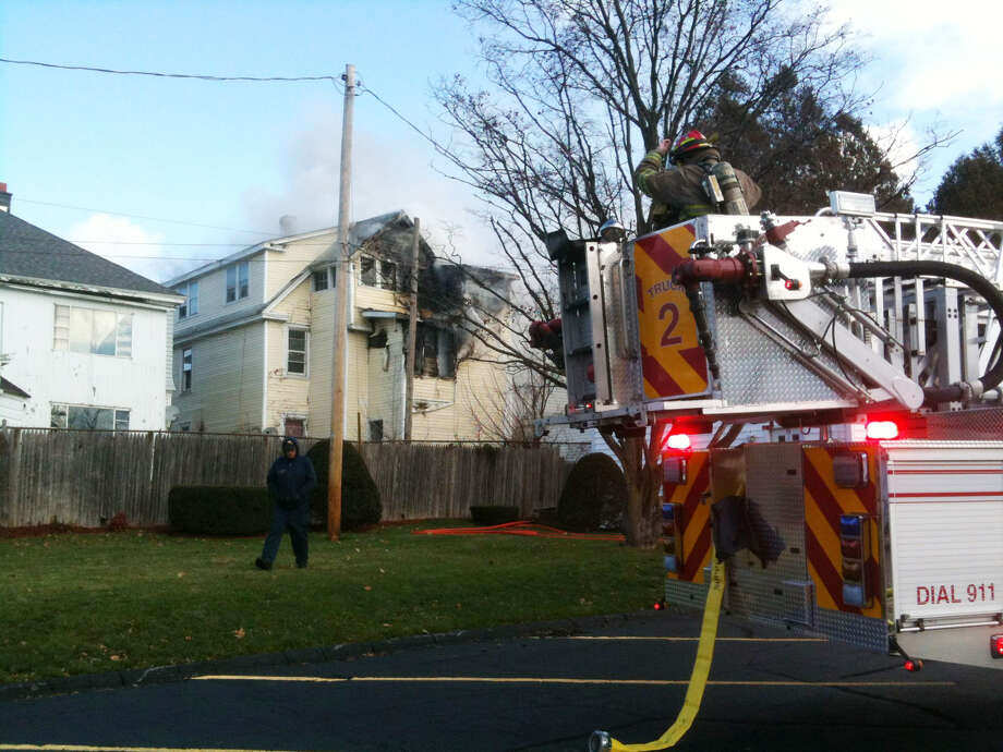 Schenectady firefighters pour water onto the rear of a two-story home on Rugby Road at around 11 a.m. Tuesday.  Flames appeared to be coming from the rear, second-floor area of the two-family house just east of McClelland Street. Several Schenectady Fire Department apparatus were on the scene and other details were not immediately available. (Mike Spain / Times Union) Photo: Spain