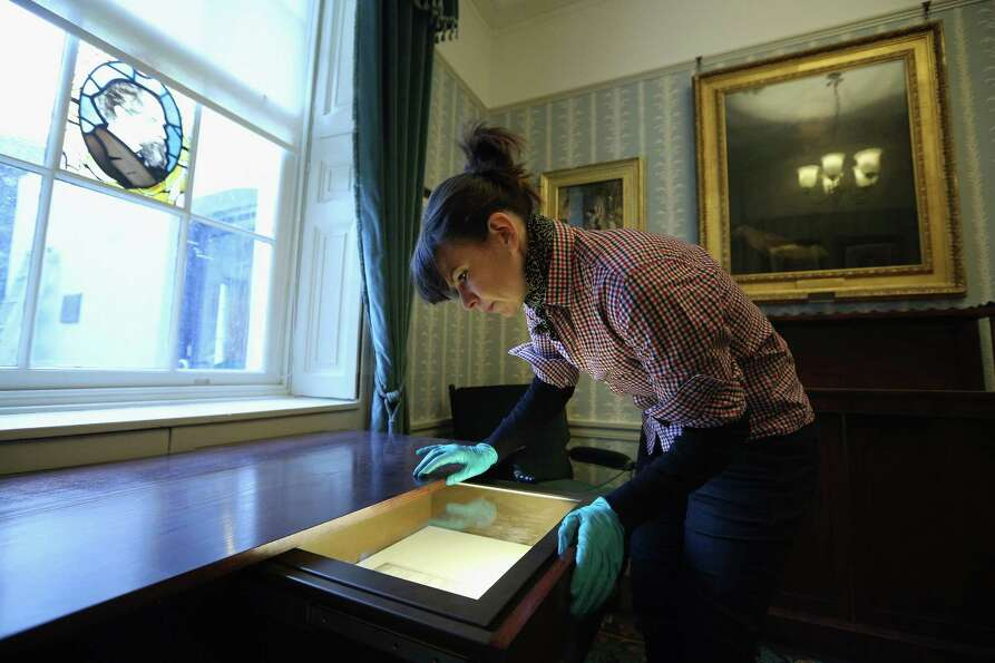 LONDON, ENGLAND - DECEMBER 07:  A woman inspects Dickens' marriage certificate in the Morning Room i