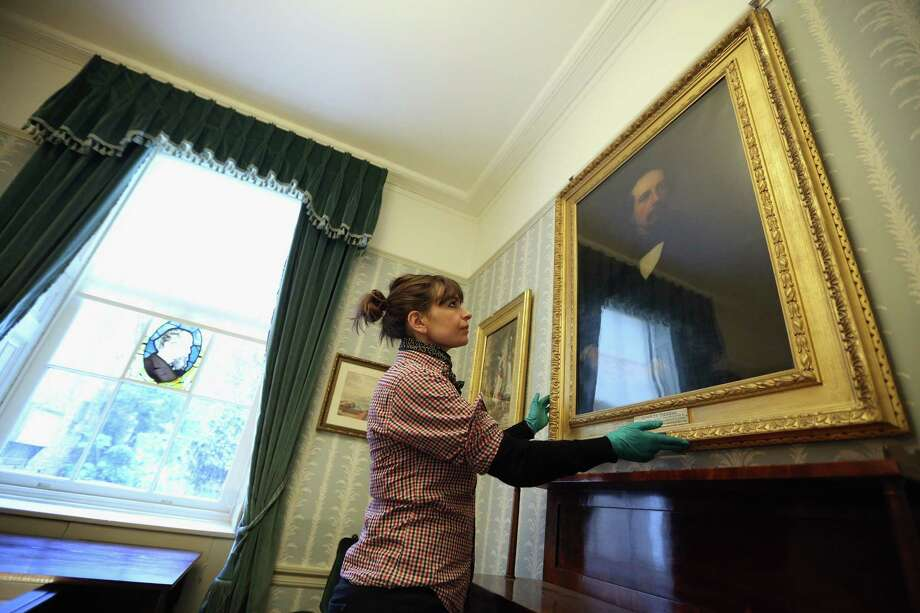 LONDON, ENGLAND - DECEMBER 07:  A woman adjusts the picture frames in the Morning Room inside the Charles Dickens Museum on December 7, 2012 in London, England. The museum will re-open to the public on December 10, 2012 following a major 3.1 million GBP refurbishment and expansion programme to celebrate Dickens' bicentenary year. The museum is located in Charles Dickens' house on Doughty Street where he lived from 1837 until 1839 and in which he wrote many novels including Oliver Twist and Nicholas Nickleby. Photo: Oli Scarff, Getty Images / 2012 Getty Images