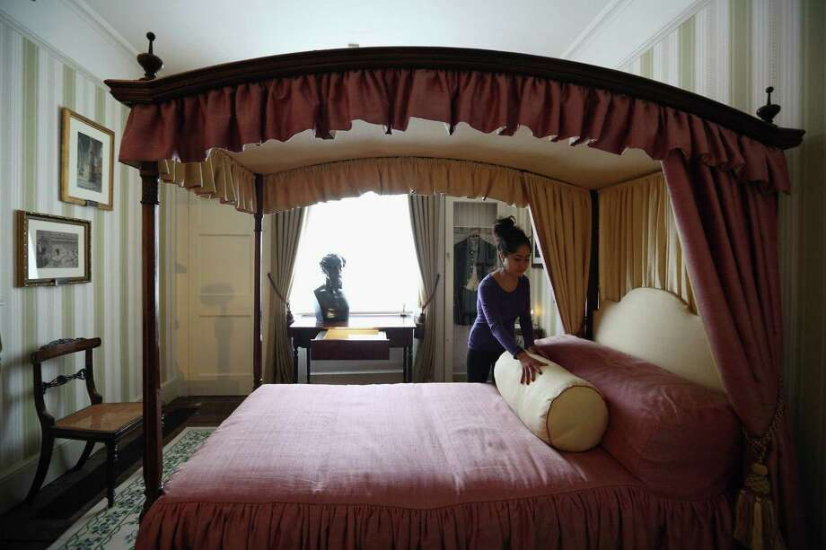 LONDON, ENGLAND - DECEMBER 07:  A woman adjusts the bed linen in a bedroom inside the Charles Dickens Museum on December 7, 2012 in London, England. The museum will re-open to the public on December 10, 2012 following a major 3.1 million GBP refurbishment and expansion programme to celebrate Dickens' bicentenary year. The museum is located in Charles Dickens' house on Doughty Street where he lived from 1837 until 1839 and in which he wrote many novels including Oliver Twist and Nicholas Nickleby. Photo: Oli Scarff, Getty Images / 2012 Getty Images