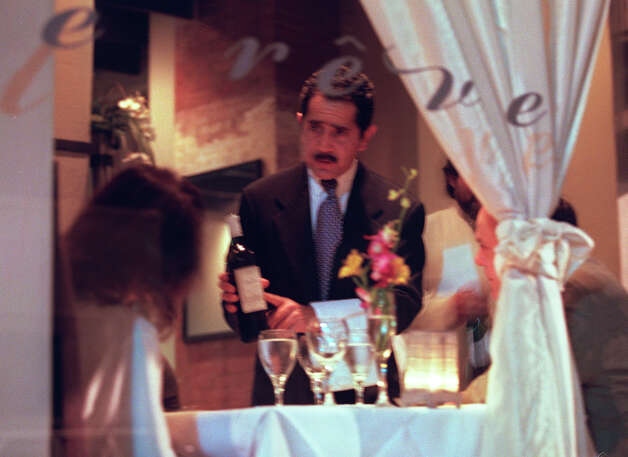 Maitre de Rudy Souberbielle shows a wine to patrons at Le Rêve restaurant on the River Walk in 2001. Weissman's Le Rêve closed in 2009 so he could focus on The Sandbar and Il Sogno. Photo: Rick Hunter