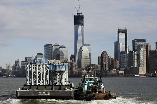 A barge loaded with sections of spire for One World Trade Center, left, is guided by tugboat across New York Harbor  from New Jersey's Port Newark, Tuesday, Dec. 11, 2012 in New York. The nine pieces each weigh 70 tons. The spire is expected to rise into the Manhattan sky by spring. Photo: Mark Lennihan, Associated Press