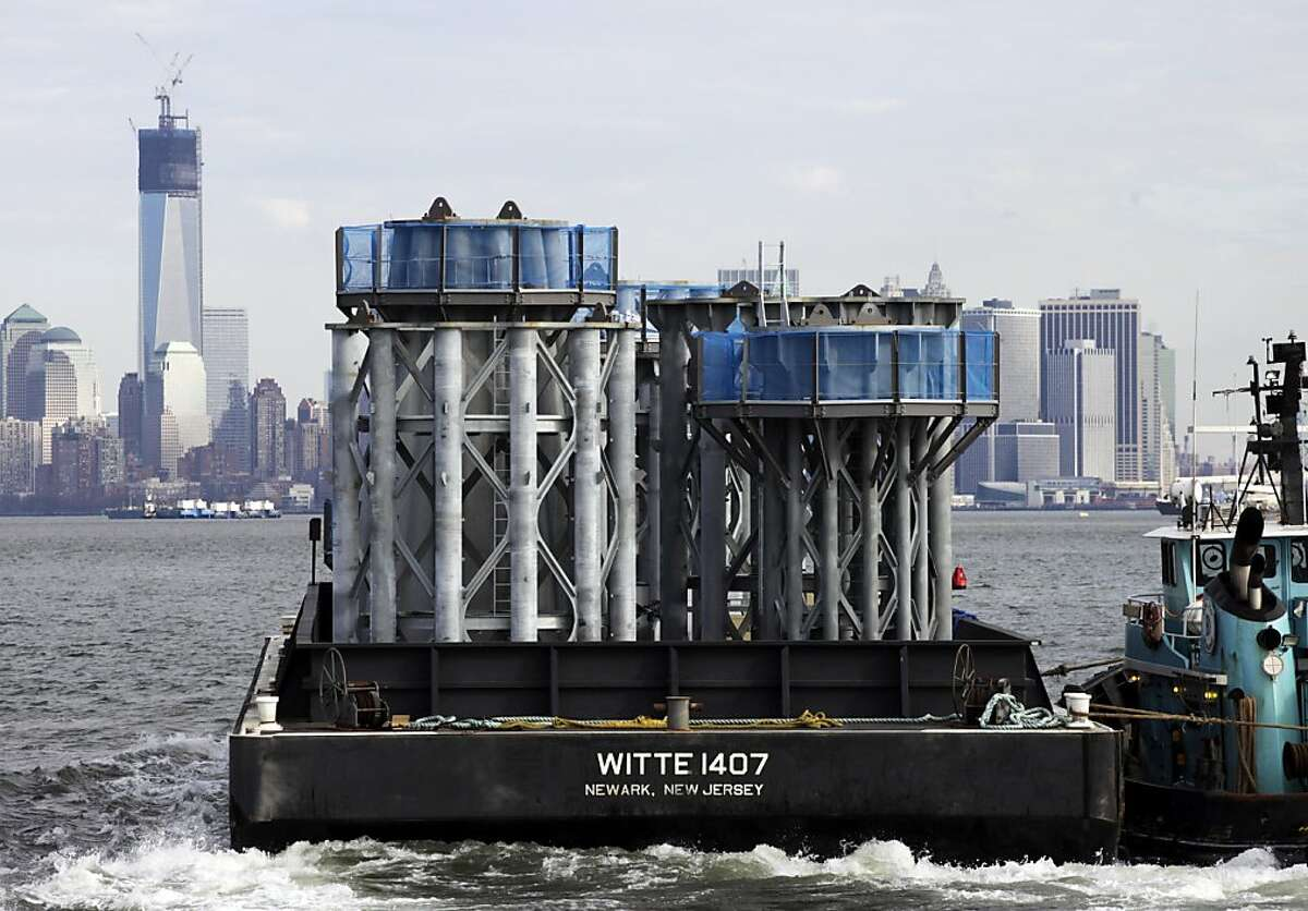 A barge loaded with sections of spire for One World Trade Center, left, is guided by tugboat across New York Harbor, Tuesday, Dec. 11, 2012 in New York.