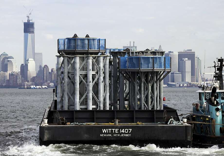 A barge loaded with sections of spire for One World Trade Center, left, is guided by tugboat across New York Harbor, Tuesday, Dec. 11, 2012 in New York. Photo: Mark Lennihan, Associated Press