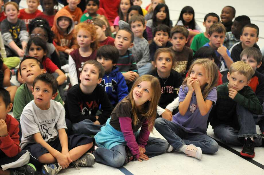 First-graders at Falcon Pass Elementary, including Paige Coon, 7, and Gracy Lane, 6, center, watch as narrator Mary Goeckler of the Houston Symphony League Bay Area demonstrates a musical instrument. First-graders at Falcon Pass Elementary, including Paige Coon, 7, and Gracy Lane, 6, center, watch as narrator Mary Goeckler of the Houston Symphony League Bay Area demonstrates a musical instrument. Photo: Jerry Baker, Freelance