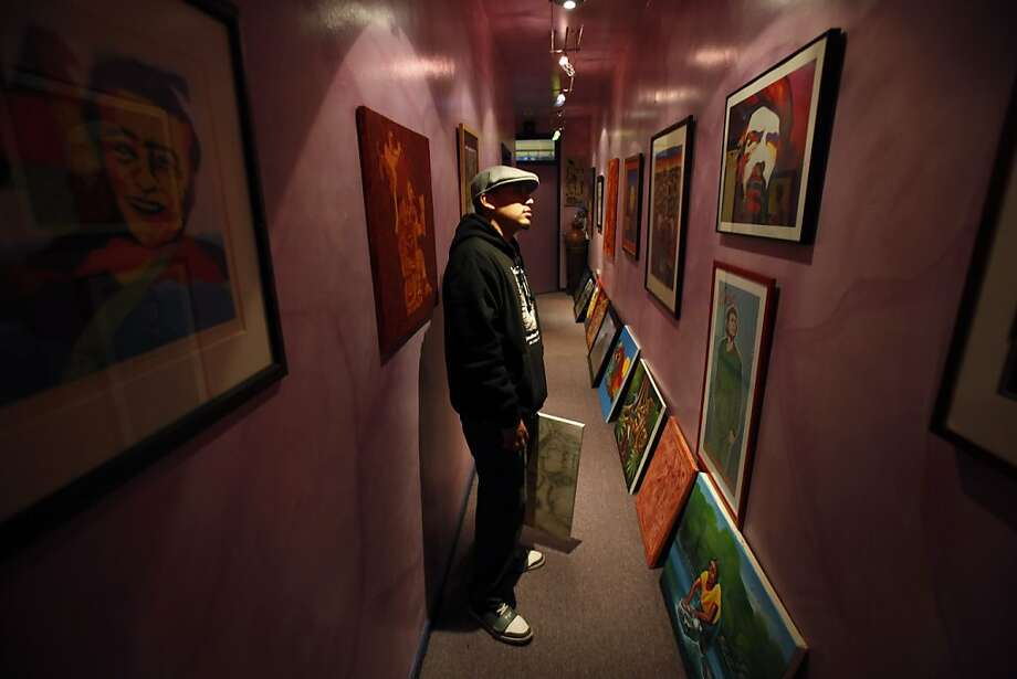 Victorino Cartagena checks out artwork on the walls of Roberto Hernandez's home in San Francisco, Calif., on Tuesday, November 27, 2012. Hernandez is an artist and has taken to training neighborhood kids how to paint low riders to keep them out of trouble in the Mission district of San Francisco, Calif. Photo: Carlos Avila Gonzalez, The Chronicle