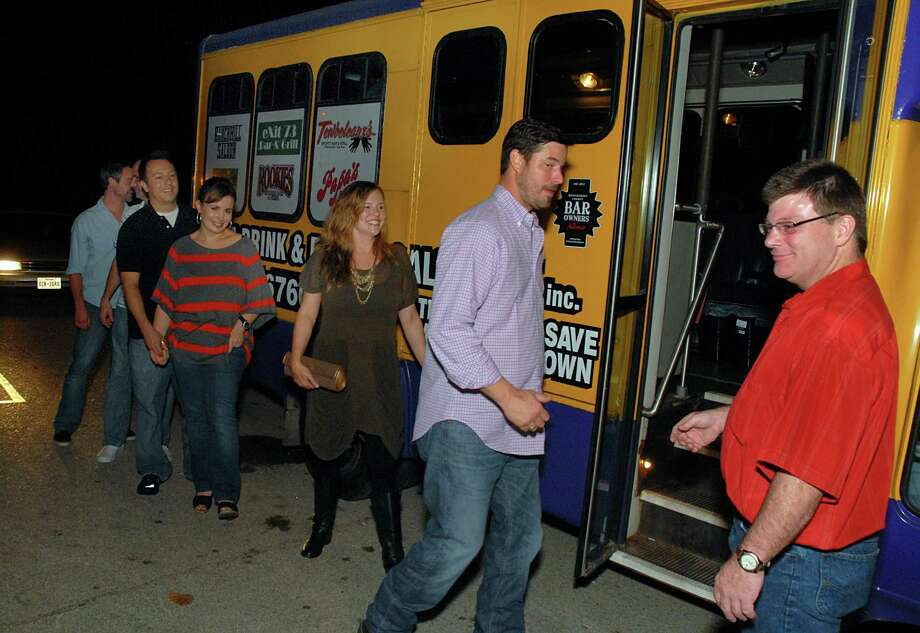 Shuttle bus driver John Steeland, right, watches as customers Brent Rabel, from left, Russell Whitmire, Matthew and Jenni Falgione, Kristin McCabe and Luke Ford, all of The Woodlands, climb on the Montgomery County Bar Owners Alliance and WALT Inc. shuttle service bus for a trip to another bar. The shuttle offer rides, for a fee, to bars in south Montgomery County. Photo: David Hopper, Freelance / freelance